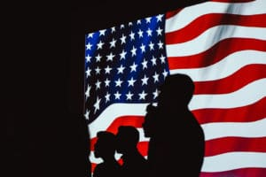 silhouettes in front of the American flag - Dan Moisand discusses if the 2020 presidential election will make the market crash